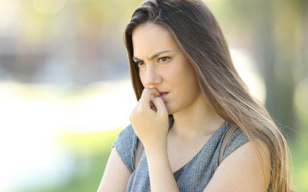nervous woman biting nails and looking away alone outdoors in the street